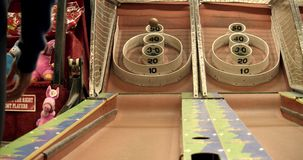 People playing skee ball at the fair. Ball being thrown at skee ball target at an amusement park at night stock footage