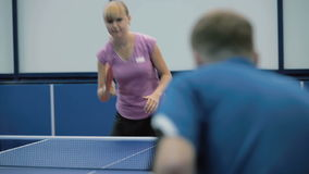 People playing a table tennis on the court. Shooting from the back of the young man. The woman come to the table. Pretty woman hits the ball and strart playing a stock footage
