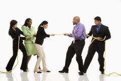People playing tug of war. Multi-ethnic businessmen playing tug of war against businesswomen stock photos