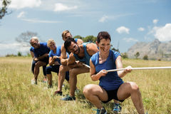 People playing tug of war during obstacle training course. In boot camp royalty free stock photo