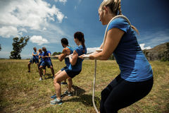 People playing tug of war during obstacle training course. In boot camp Stock Images
