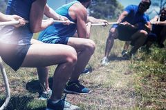 People playing tug of war during obstacle training course. In boot camp stock photo