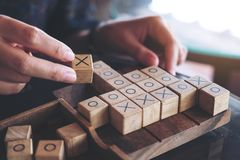 People playing wooden Tic Tac Toe game or OX game. Closeup image of people playing wooden Tic Tac Toe game or OX game Royalty Free Stock Photography