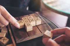 People playing wooden Tic Tac Toe game or OX game. Closeup image of people playing wooden Tic Tac Toe game or OX game Royalty Free Stock Images