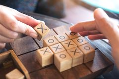 People playing wooden Tic Tac Toe game or OX game. Closeup image of people playing wooden Tic Tac Toe game or OX game Stock Image