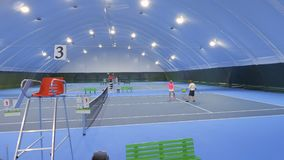 People plays tennis at indoors tennis courts. View from flying drone. People plays tennis at indoors tennis courts. Two men have a competition. The woman trains stock video