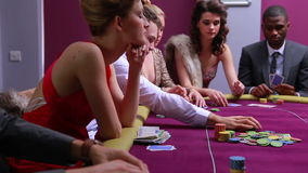 People at poker table placing bets woman in red dress going all in stock video footage