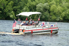 People on pontoon in parade on the river to celebrate Independence Day, the Fourth of July. A group of people on a decorated pontoon parade on Independence day stock images