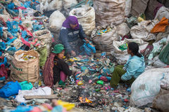 People from poorer areas working in sorting of plastic on the dump. Stock Photos
