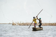 People in PORTO-NOVO, BENIN. PORTO-NOVO, BENIN - MAR 9, 2012: Unidentified Beninese father throws the fish net into the water and his son helps him. People of royalty free stock image