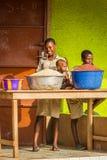 People in PORTO-NOVO, BENIN. PORTO-NOVO, BENIN - MAR 9, 2012: Unidentified Beninese girl sells cereals with her children. People of Benin suffer of poverty due stock images