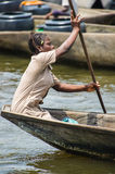 People in PORTO-NOVO, BENIN. PORTO-NOVO, BENIN - MAR 9, 2012: Unidentified Beninese woman sails a wooden boat. People of Benin suffer of poverty due to the Stock Photography