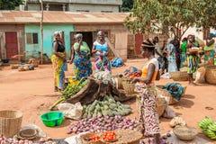 People in PORTO-NOVO, BENIN. PORTO-NOVO, BENIN - MAR 9, 2012: Unidentified Beninese woman sells garlic and tomatoes at the local market. People of Benin suffer stock photo
