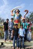 People posing in front of demon Mahishasura statue Stock Photos