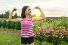 People, power, stamina, strength, health, sport, fitness concept. Outdoor portrait smiling teenage girl flexing her muscles, backg. Round green lawn sunset royalty free stock photo
