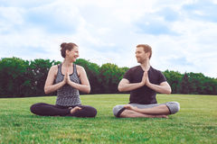 People practice acro yoga outdoors healthy lifestyle. Man and women practice acro yoga in the park meditation Stock Images