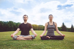 People practice acro yoga outdoors healthy lifestyle. Man and women practice acro yoga in the park meditation Stock Photo