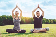 People practice acro yoga outdoors healthy lifestyle. Man and women practice acro yoga in the park meditation Royalty Free Stock Images