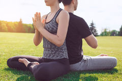 People practice acro yoga outdoors healthy lifestyle. Man and women practice acro yoga in the park meditation Stock Image