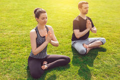 People practice acro yoga outdoors healthy lifestyle. Man and women practice acro yoga in the park meditation Royalty Free Stock Image
