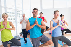 People practicing tree pose in fitness studio Stock Images