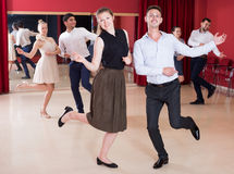 People practicing twist movements. Young smiling people practicing vigorous twist movements in dance class Royalty Free Stock Photos