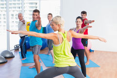 People practicing warrior pose in fitness club Royalty Free Stock Photo