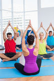 People practicing yoga in fitness club Stock Photography