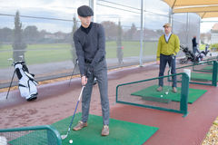 People practise golf at city centre golf driving range Royalty Free Stock Image
