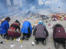 People Pray Before Burning Joss Paper in China. Ethnic minorities (Bai minorities) from the Yunnan province of China pray in front of a burning pile of joss stock photo