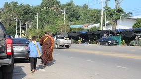People pray with monk and put food offerings to Buddhist alms bowl. In morning time at Ratchaburi, Thailand. Suan Phueng (Thai stock video