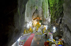 People praying with buddha statue inside cave at Wat Tham Khao Y Stock Image