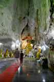 People praying with buddha statue inside cave at Wat Tham Khao Y Stock Images