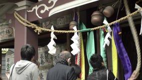 People praying at Buddhist shrine stock video