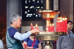 People praying with candles at temple in Melaka, Malaysia stock photo