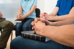 People praying. Close-up Of People Praying With Holy Bible Stock Image