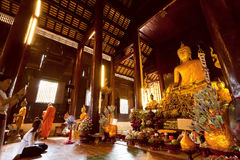 People praying inside sunny hall of historical wooden temple with golden Buddha statue Royalty Free Stock Photos