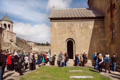 People praying near the historical walls of the christian Svetitskhoveli Cathedral, UNESCO World Heritage Site. Royalty Free Stock Image