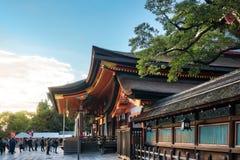 People praying at Yasaka Shrine Honden in Kyoto, Japan. Kyoto, Japan -November 2, 2018: People praying and visiting Yasaka Shrine Honden on a beautiful sunny day royalty free stock image