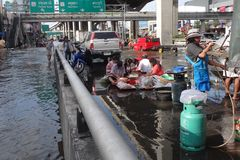 People prepare some free food to be distributed  in a flooded street in Rangsit, Thailand, in October 2011.  Royalty Free Stock Image