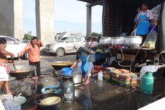 People prepare some free food to be distributed  in a flooded street in Rangsit, Thailand, in October 2011.  Stock Images
