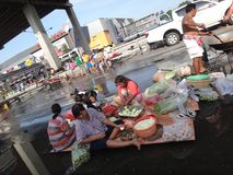 People prepare some free food to be distributed  in a flooded street in Rangsit, Thailand, in October 2011.  Stock Photos