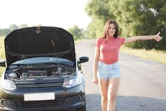 People and problems with transport. Attractive unexperienced female driver makes stop gesture on road, stands near brocken car, fe stock photography