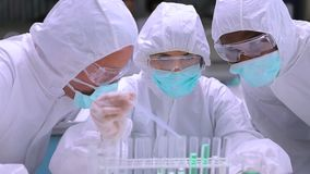 People in protective suits adding green liquid to test tubes with two other chemists watching. People in protective suits  adding green liquid to test tubes with stock footage