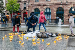 People protesting manifestation die-in against immigration policy and border management. STRASBOURG, FRANCE - APR 26 2015 Arranging Frontex line over dead corps stock image