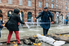 People protesting manifestation die-in against immigration policy and border management. STRASBOURG, FRANCE - APR 26 2015 Arranging Frontex line over dead corps royalty free stock image