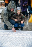 People protesting manifestation die-in against immigration policy and border management. STRASBOURG, FRANCE - APR 26 2015: Dad and son at protest against stock photos
