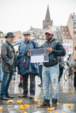 People protesting manifestation die-in against immigration policy and border management. STRASBOURG, FRANCE - APR 26 2015: I am a migrant poster holed by a man stock photos