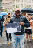 People protesting manifestation die-in against immigration policy and border management. STRASBOURG, FRANCE - APR 26 2015: I am a migrant poster holed by a man royalty free stock image