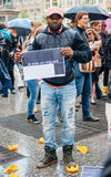 People protesting manifestation die-in against immigration policy and border management. STRASBOURG, FRANCE - APR 26 2015: I am a migrant poster holed by a man stock images